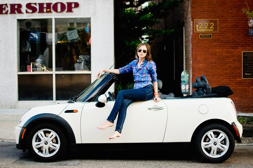Stock Photo: 4152-155 Woman sitting on a car in front of a store