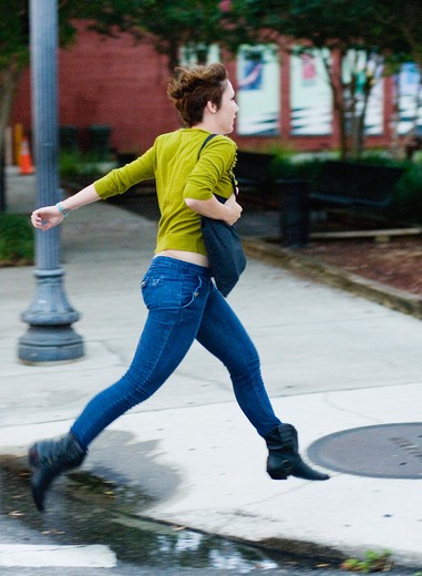 Woman running on a footpath : Stock Photo