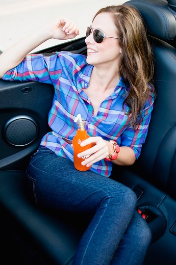 Woman sitting in a car and smiling : Stock Photo
