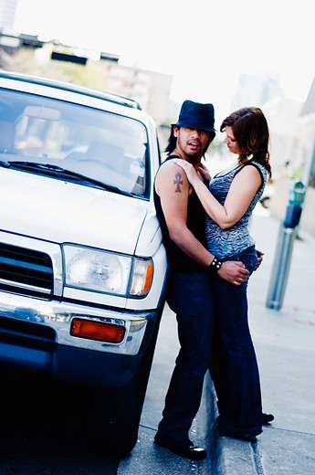 Romantic couple on a street beside a car : Stock Photo