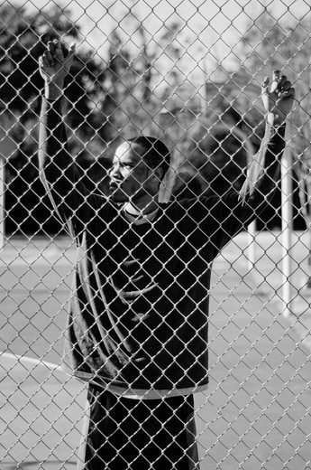 Basketball player holding chainlink fence : Stock Photo