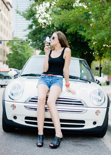 Stock Photo: 4152-199 Woman sitting on the car hood and smoking a cigar