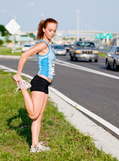 Stock Photo: 4152-218 Female Athlete stretching at roadside