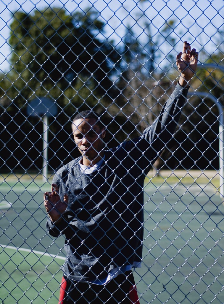 Basketball player looking through a chainlink fence : Stock Photo
