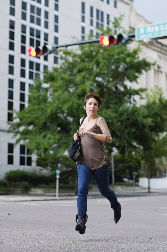 Woman running on a road : Stock Photo