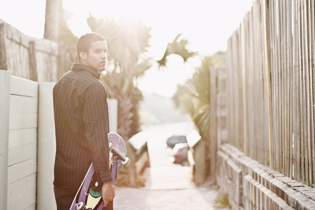 Stock Photo: 4152-248 Young man holding a skateboard