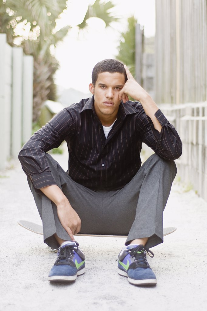 Stock Photo: 4152-253 Young man sitting on a skateboard and looking sad