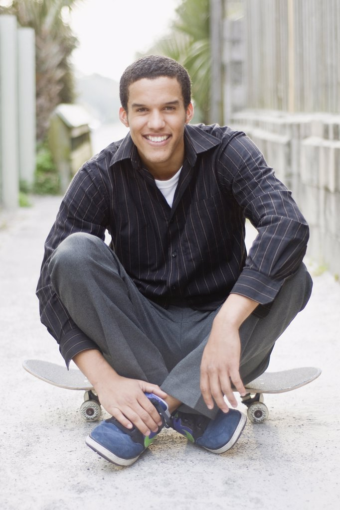 Stock Photo: 4152-264 Young man sitting on a skateboard and smiling