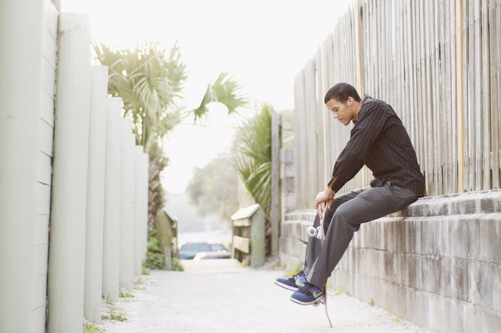 Young man sitting on a wall and holding a skateboard : Stock Photo