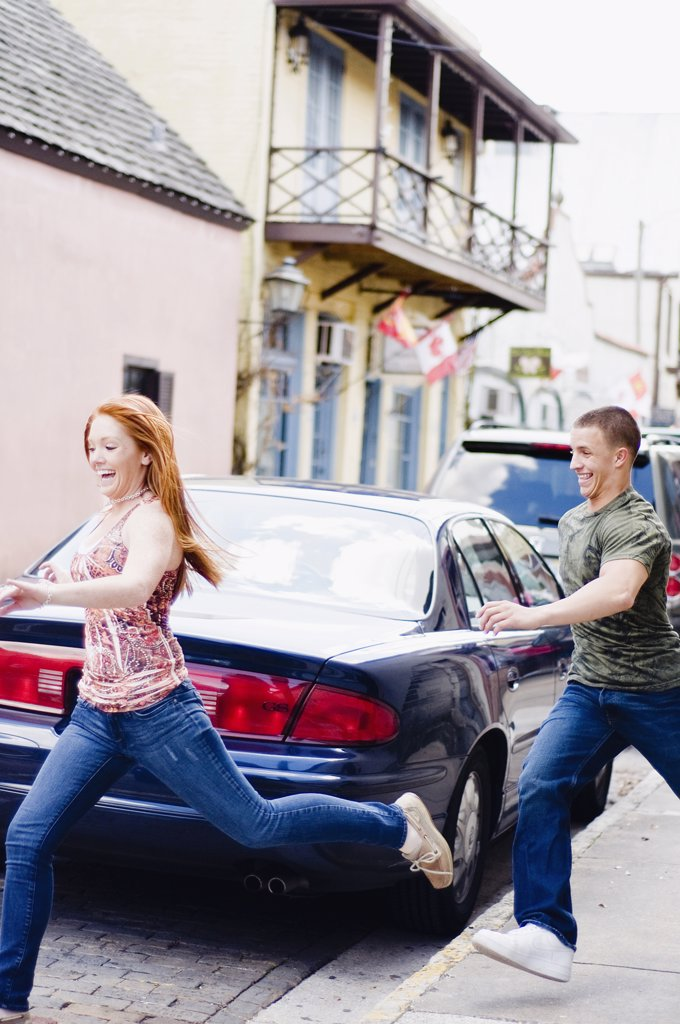 Young couple running on a street : Stock Photo