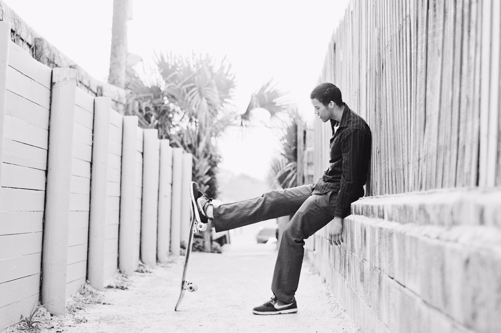 Young man sitting on a wall and playing with a skateboard : Stock Photo