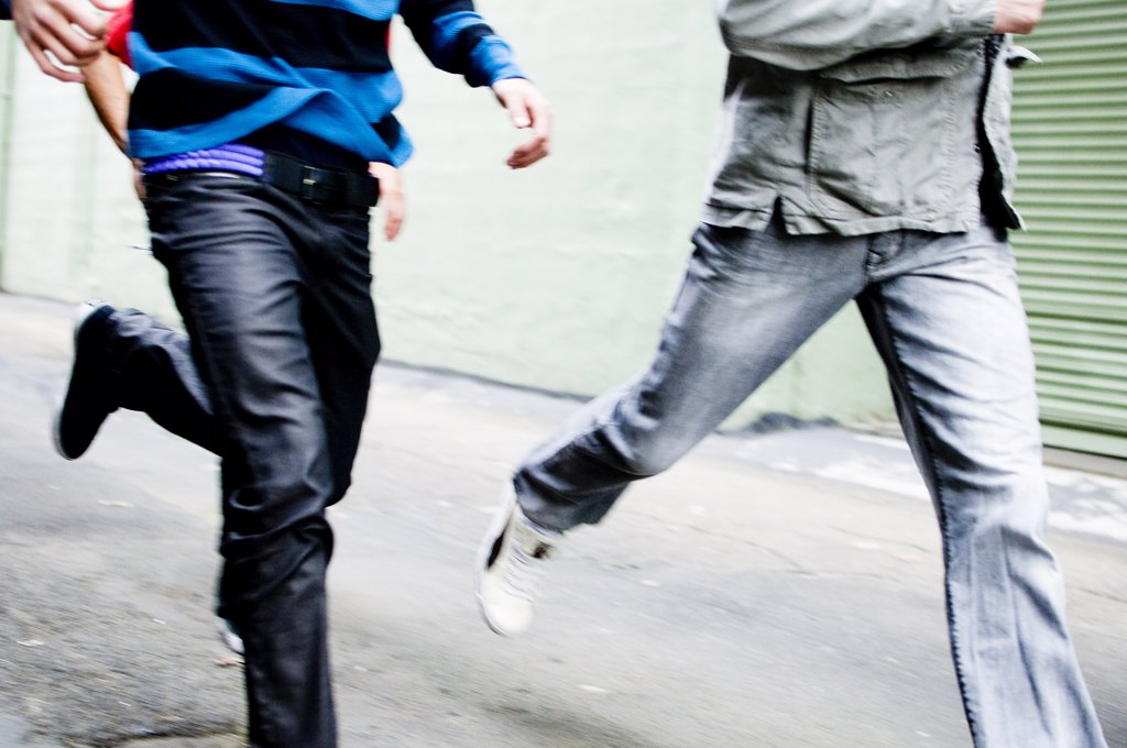 Low section view of two men running : Stock Photo