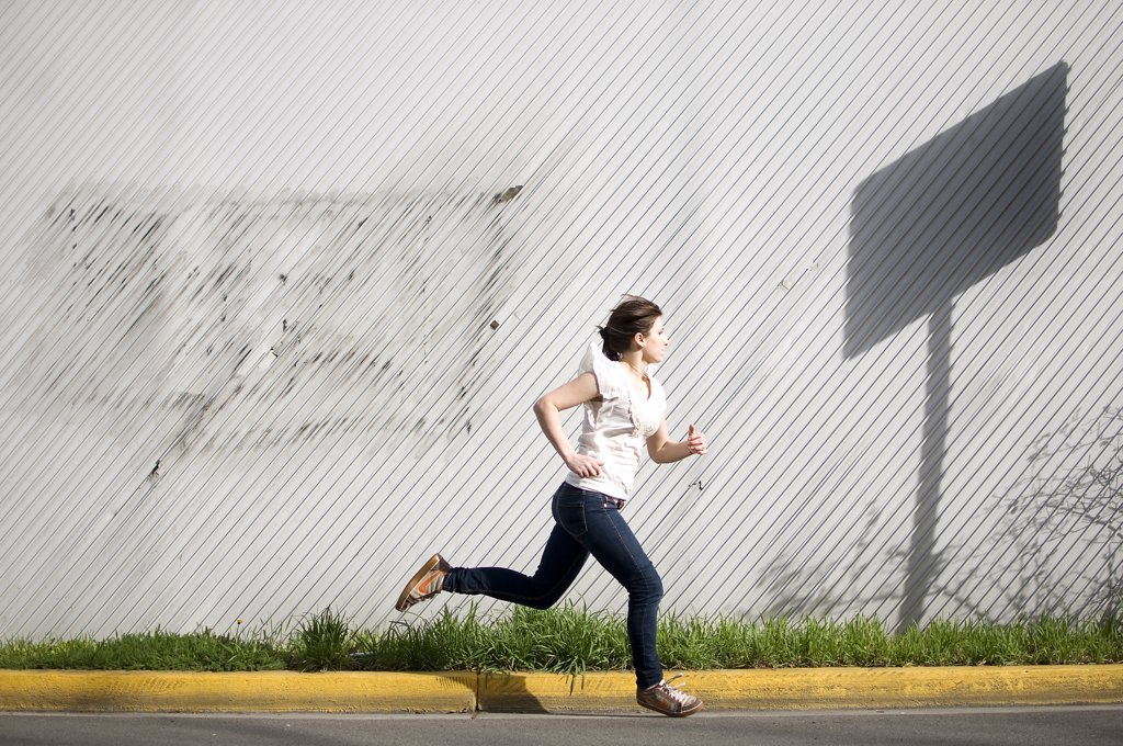 Young woman running on a street : Stock Photo
