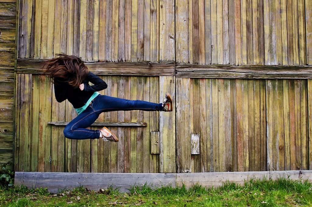 Young woman jumping and kicking in air : Stock Photo