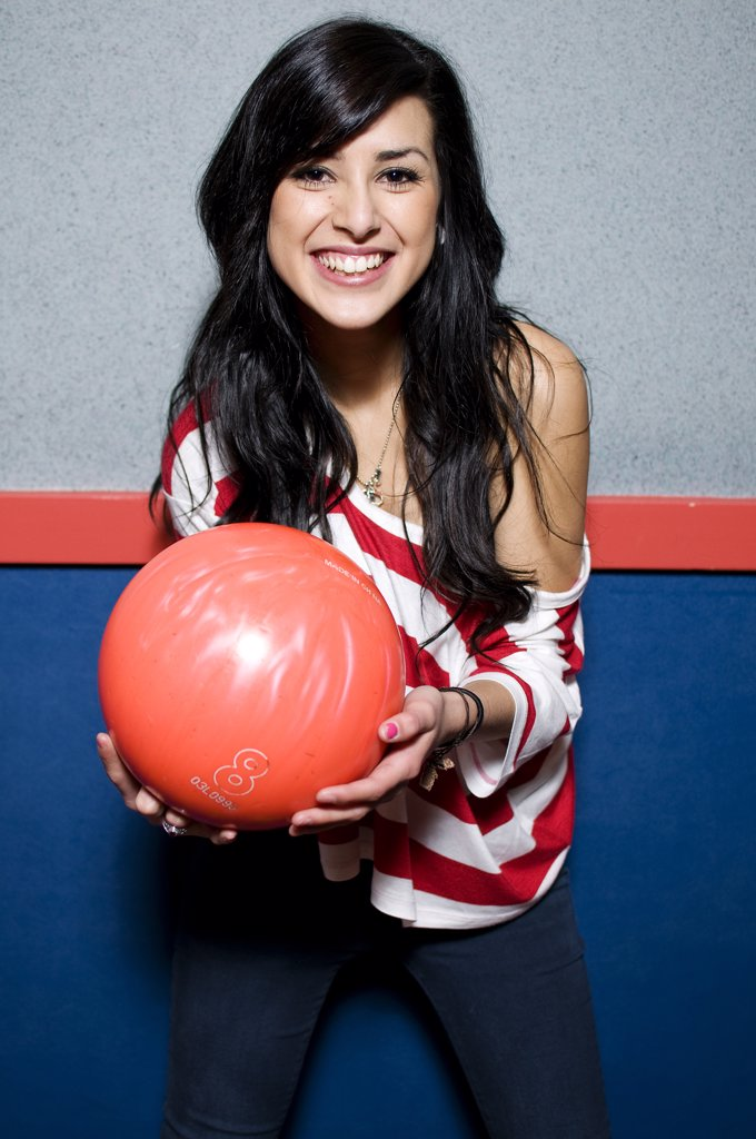 Stock Photo: 4152-297F Young woman holding a bowling ball and smiling