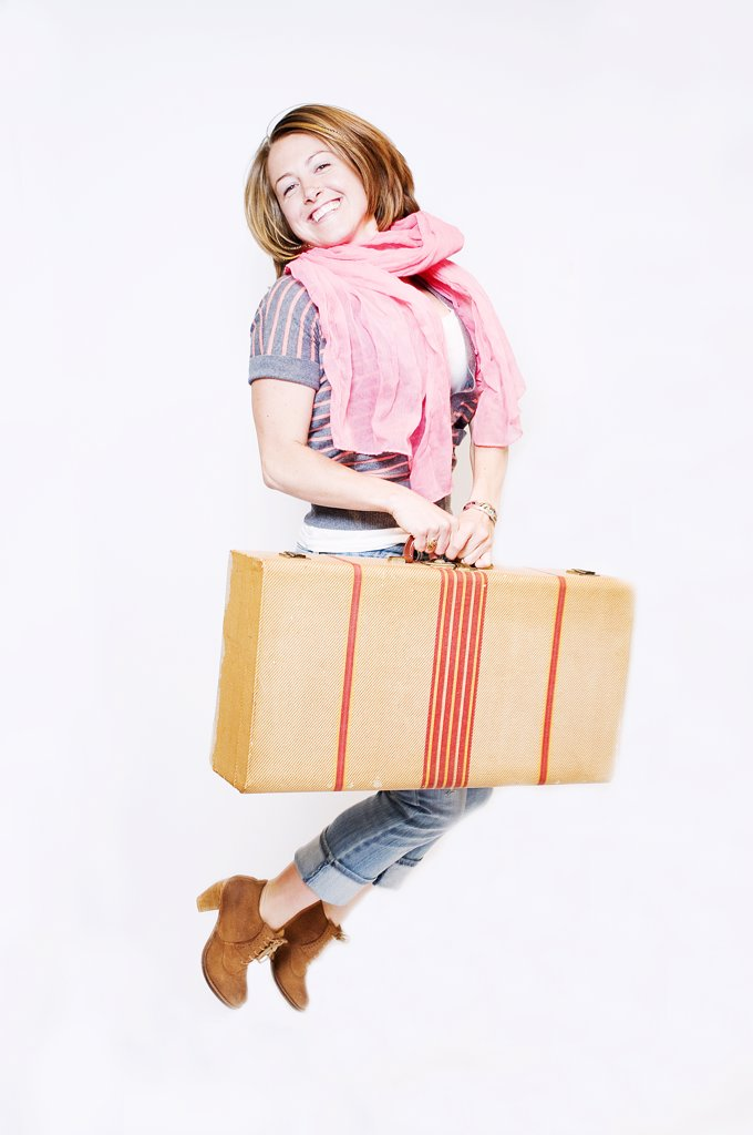 Stock Photo: 4152R-301 Young woman with suitcase jumping