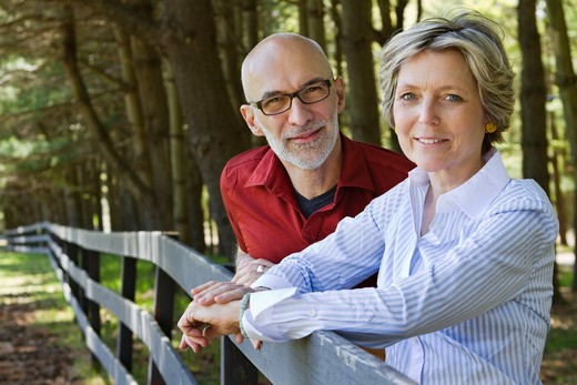 Outdoor portrait of mature couple smiling and leaning on wooden fence : Stock Photo