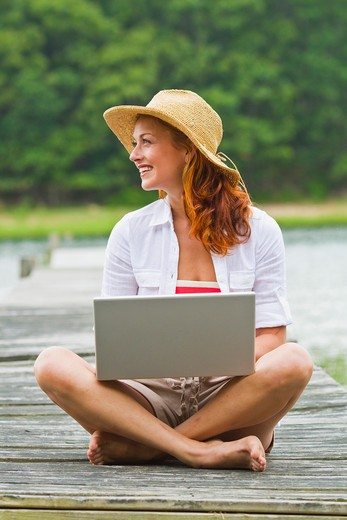 Young woman wearing straw hat using laptop on jetty : Stock Photo