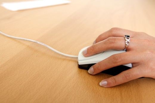 A businesswoman using a mouse : Stock Photo