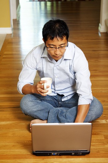 An asian businessman sitting on the floor and working on his laptop at home : Stock Photo