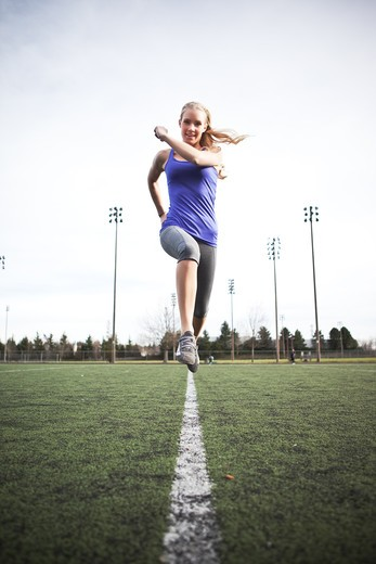 A beautiful caucasian woman exercises in a sport field : Stock Photo