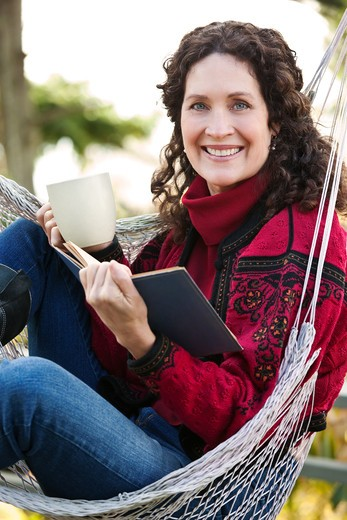 Stock Photo: 4157R-2381 A beautiful mature woman sitting on a hammock reading a book