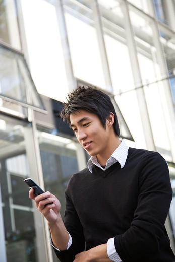 Stock Photo: 4157R-2617 A casual asian man texting on his cellphone