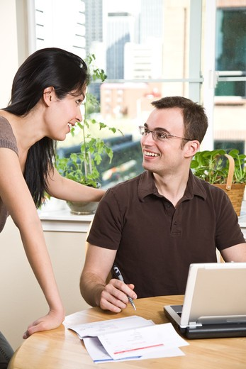 Stock Photo: 4157R-3455 A happy couple paying bills by using online banking at home
