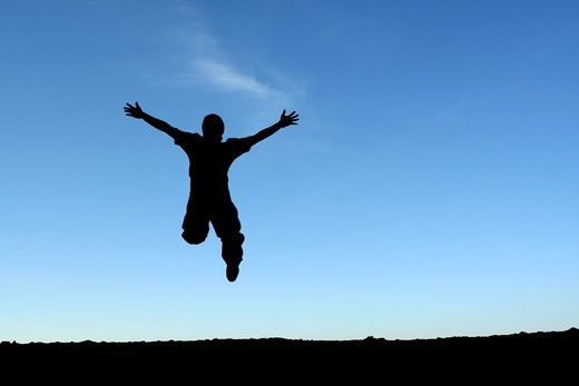 A happy man jumping in the air, in silhouette : Stock Photo