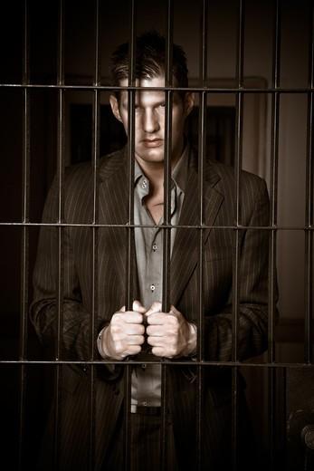 Stock Photo: 4157R-4846 A caucasian businessman sitting in jail handcuffed