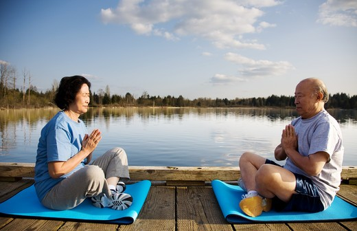 Stock Photo: 4157R-5034 A shot of a senior couple practicing a yoga exercise and meditating outdoor