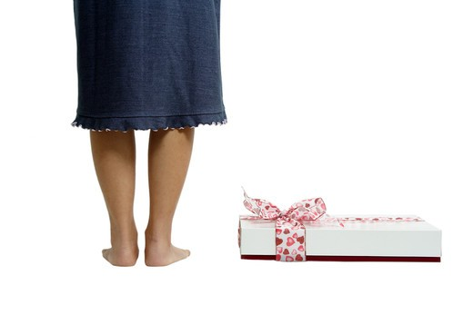 A woman standing next to a gift box : Stock Photo
