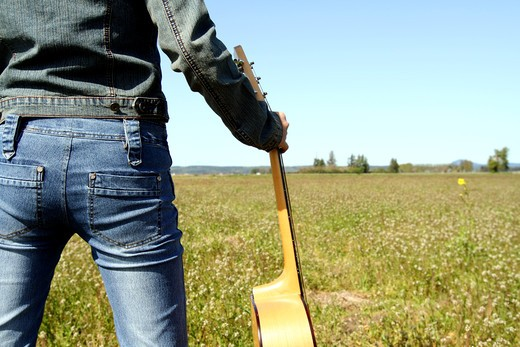 A woman holding a guitar looking at an empty field : Stock Photo
