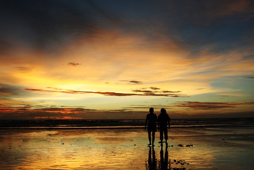 Two people in silhouette walking on a beach during sunset : Stock Photo