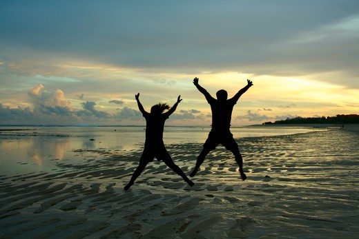 Two people in silhouette jumping happily on a beach : Stock Photo
