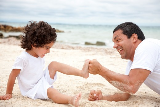 Stock Photo: 4158R-10625 Man and son at the beach competing