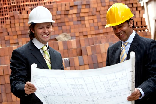 Engineers at a construction site looking at the blueprints : Stock Photo