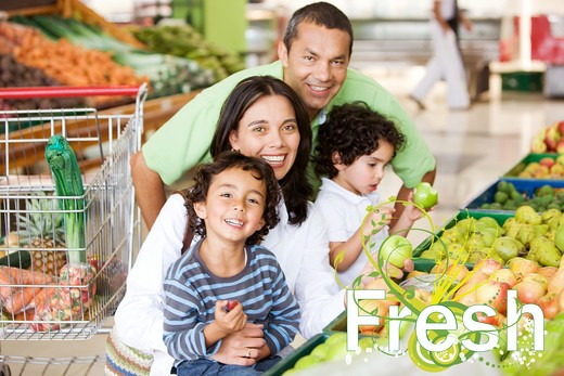 Happy family at the supermarket buying groceries : Stock Photo