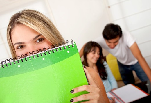 Female student covering her face with a notebook : Stock Photo