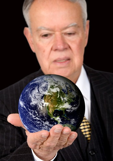 business man holding a globe over a black background - globe is from http://www.nasa.gov : Stock Photo