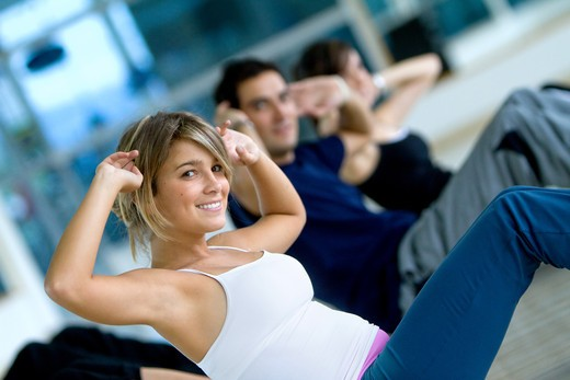 group of people at the gym smiling an doing abs exercises : Stock Photo