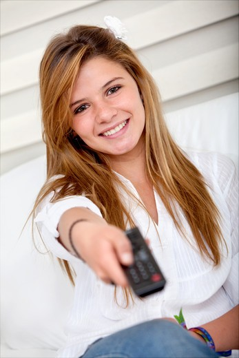 Girl holding a remote control and smiling : Stock Photo