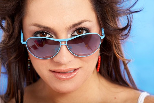 fashion or casual woman portrait wearing sunglasses giving a big smile over a blue background : Stock Photo