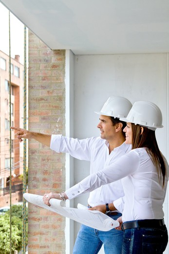 Architects with blueprints at a construction site : Stock Photo