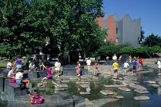 GERMANY, COLOGNE, CHILDREN PLAYING IN PARK IN FRONT OF ROMAN-GERMANIC MUSEUM : Stock Photo