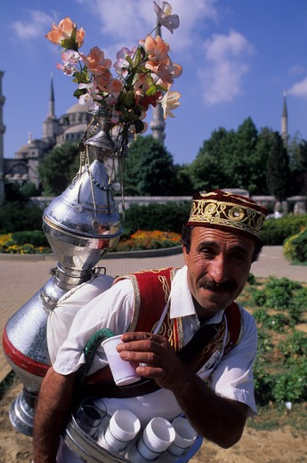 TURKEY, ISTANBUL, WATER BEARER, CLOSE-UP, BLUE MOSQUE IN BACKGROUND : Stock Photo
