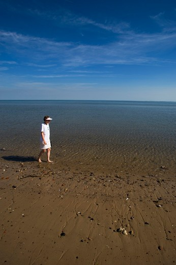 GERMANY, SCHLESWIG HOLSTEIN, NORTH SEA, NORTH FRISIAN ISLANDS, SYLT ISLAND, LIST, WOMAN WALKING ON BEACH AT LOW TIDE, MODEL RELEASED : Stock Photo