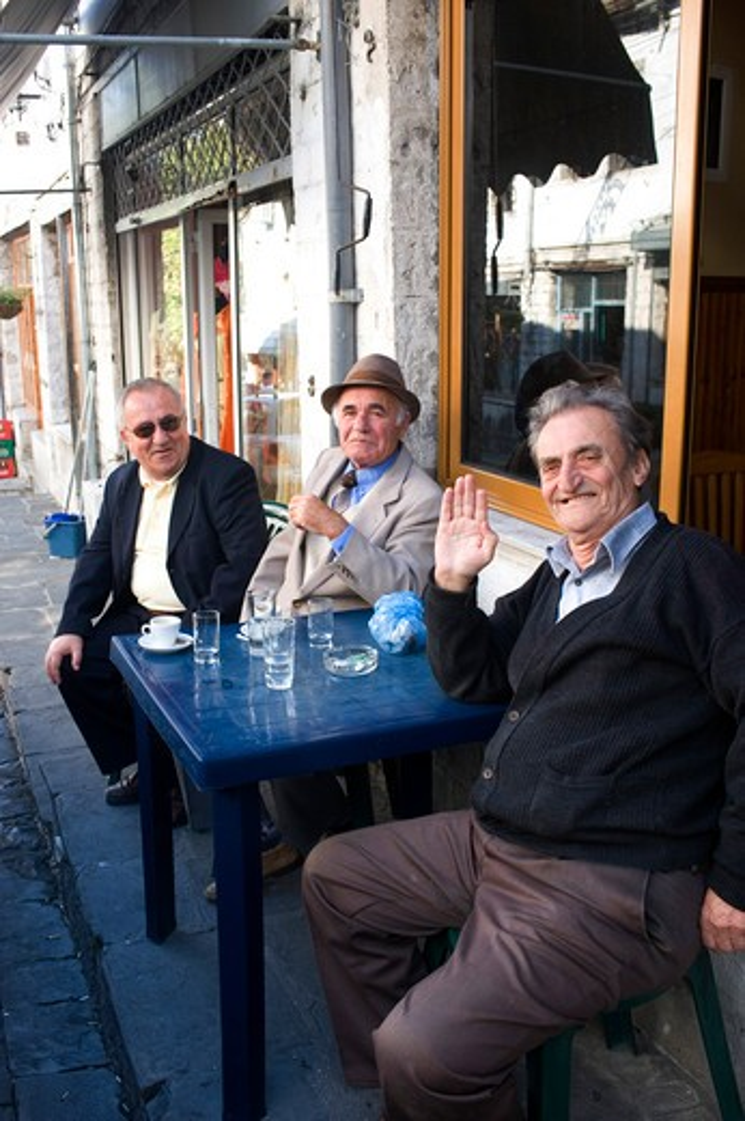 ALBANIA, GJIROKASTRA, STREET SCENE, MEN SITTING IN SIDEWALK CAFE : Stock Photo