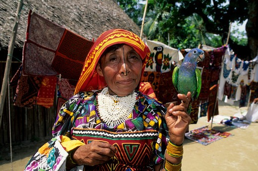 PANAMA, SAN BLAS ISLANDS, ACUATUPU ISLAND, KUNA INDIAN WOMAN WITH PET PARROT : Stock Photo