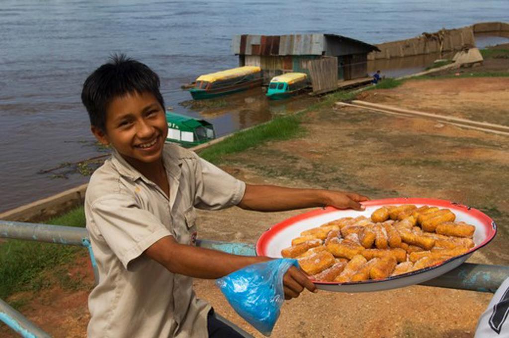 PERU, AMAZON RIVER BASIN, NEAR IQUITOS, MARANON RIVER, TOWN OF NAUTA, STREET SCENE, BOY SELLING BAKED SWEETS : Stock Photo